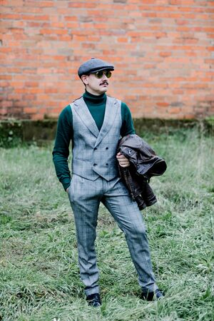 Well-dressed man wearing a grey retro suit, cap and green jersey