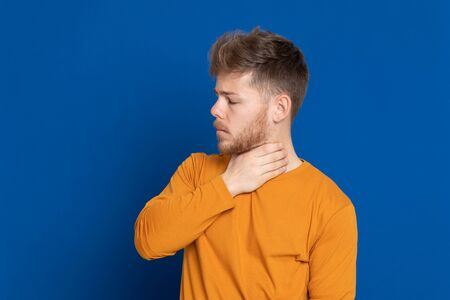 Attractive young guy with a yellow T-shirt on a blue background Stock Photo