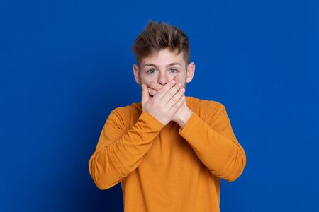 Attractive young guy with a yellow T-shirt on a blue background Imagens