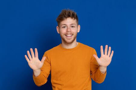 Attractive young guy with a yellow T-shirt on a blue background 스톡 콘텐츠