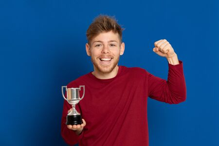 Attractive young guy with a red T-shirt on a blue background Zdjęcie Seryjne