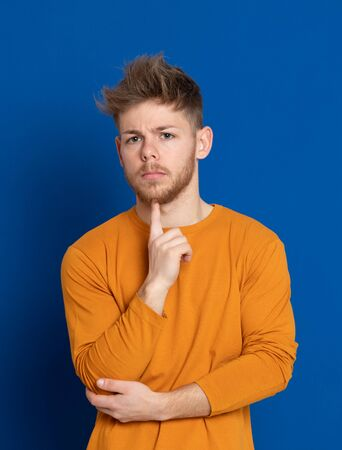 Attractive young guy with a yellow T-shirt on a blue background Zdjęcie Seryjne
