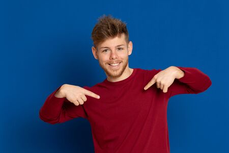 Attractive young guy with a red T-shirt on a blue background 스톡 콘텐츠