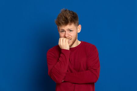 Attractive young guy with a red T-shirt on a blue background 免版税图像