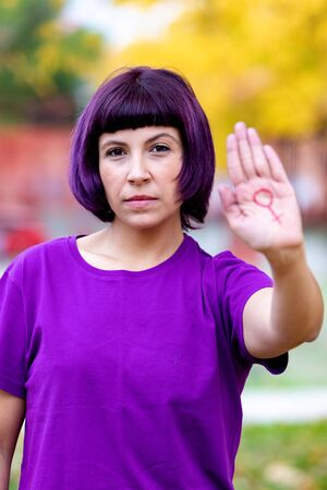 Woman wearing purple t-shirt with the female symbol drawn oh her hand