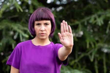 Angry woman with in purple showing the hand palm saying STOP isolated on a white background