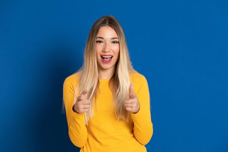 Blonde girl wearing a yellow T-shirt on a blue background