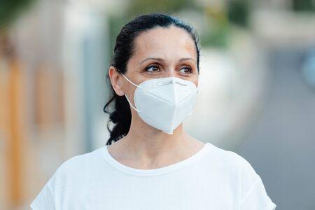 Femme mature portant un masque facial dans la rue Banque d'images