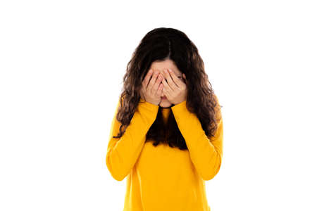 Adorable teenage girl with yellow sweater isolated on a white background