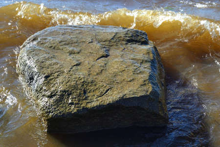 A large wet boulder lies in the water against the background of rolling waves and muddy water after small storm.