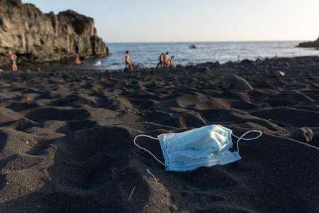Disposable face mask lying on the beach. Plastic pollution caused by Covid 19