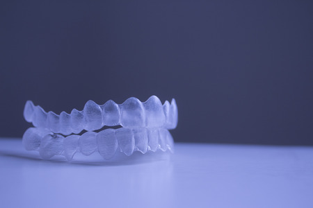 Invisible Invisalign dental braces brackets plastic teeth tooth isolated with shallow depth of focus artistic photograph. Stock Photo