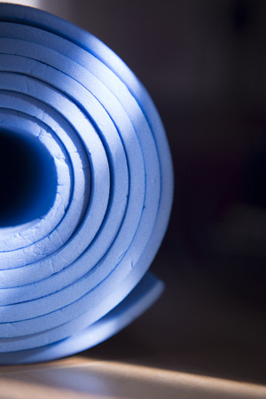 Old blue yoga mat rolled up on the floor. Stock Photo