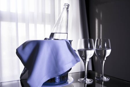 no movement: Glass table with ice bucket and open bottle of water. Two crystal glasses with water. Stock Photo
