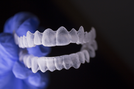 Hand with blue glove holding medical oral orthodontics Invisible