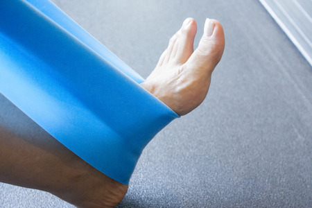 elastic band: Womans foot with elastic band performing stretching exercise Stock Photo