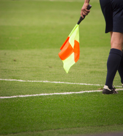 linesman: Soccer Referee with orange and yellow flag