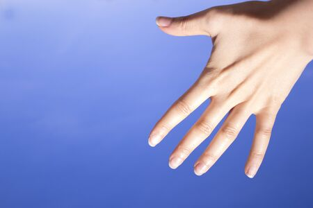 gesticulation: White woman hand gesturing on blue background Stock Photo