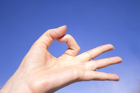 White woman hand gesturing on blue background Stock Photo