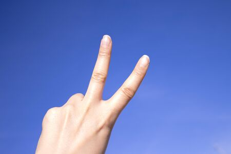 White woman hand gesturing on blue background Imagens