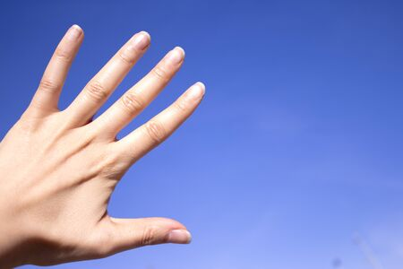gesturing: White woman hand gesturing on blue background Stock Photo