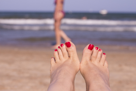 Beach scene with woman feet on the sand. Nails of feet painted red Stock Photo