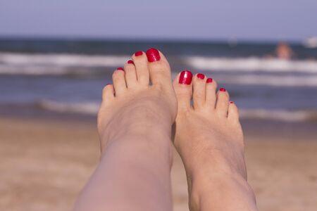 Strand scène met vrouwelijke voeten op het zand. Nagels van voeten geverfd rood