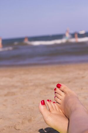 painted toenails: Beach scene with woman feet on the sand. Nails of feet painted red Stock Photo