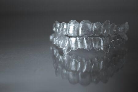 bracket: Plastic dental orthodontics on colored background. No people Stock Photo