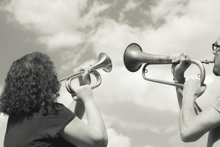 男性と女性の演奏は空を背景にトランペットします。