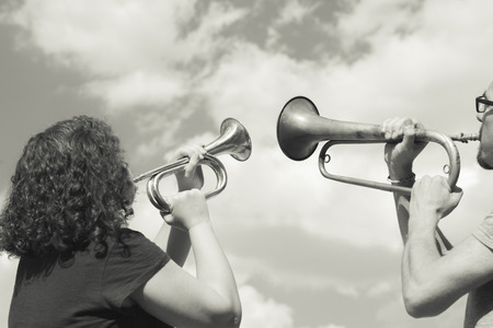 Man and woman playing trumpet on sky background