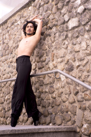 Male dancer doing a classic ballet pirouette. Urban background