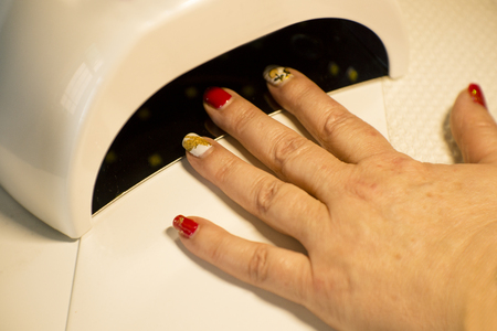 Womans hand drying nails with uv led lamp 写真素材