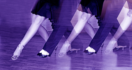 Couple of dancers dancing in bright gold and black and white shoes