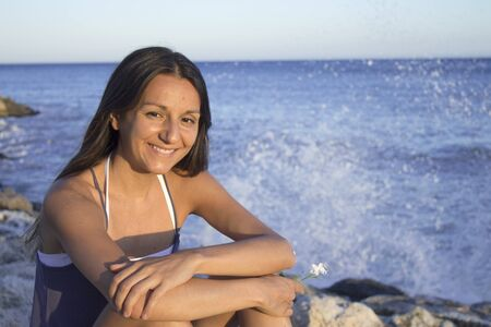 Portrait of smiling young girl with beach background at sunset