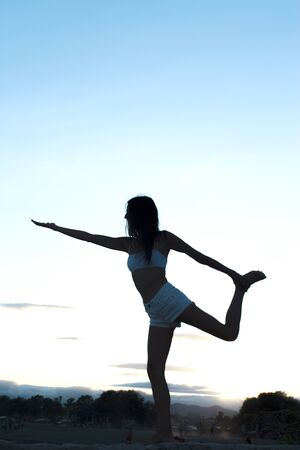 Young athlete girl doing yoga asanas with natural background