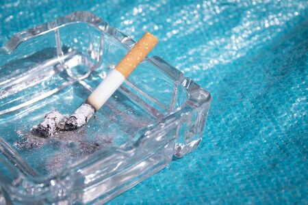 Lighted cigarette supported on ashtray. No people Stock Photo