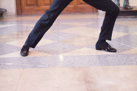 Legs of dancer man in motion. Black dress