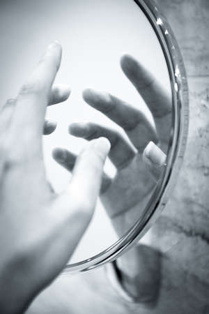 Womans hand reflected in round mirror. Mysterious scene