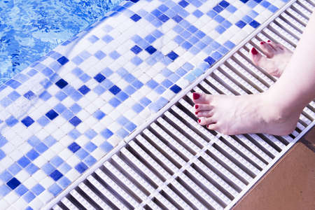 Bare feet of woman with nails painted red. Pool background 写真素材