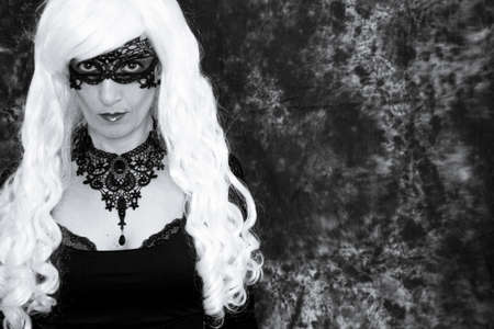 Woman disguised in gothic style for halloween party with mask 写真素材