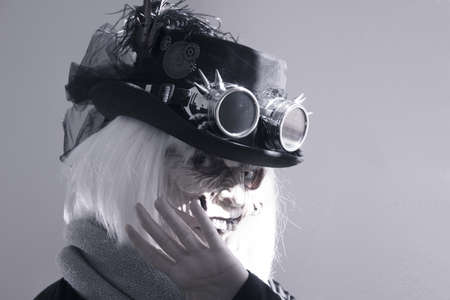Woman with monster face and black hat wearing steampunk glasses. White hair. 写真素材