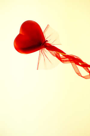 Red heart attached to a stick with a bow hanging. Copy space