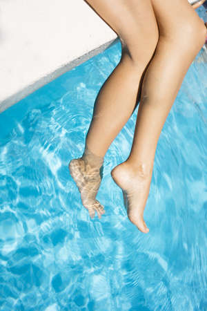 Slim legs of young woman in swimming pool. Summer time