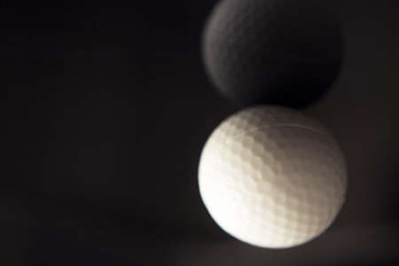 White golf ball somewhat out of focus on dark background. No people