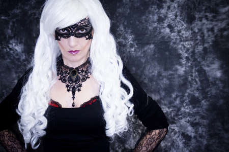 Woman disguised in gothic style for halloween party with mask Standard-Bild