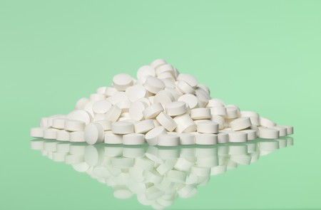 curative: Stack of pills towards green background