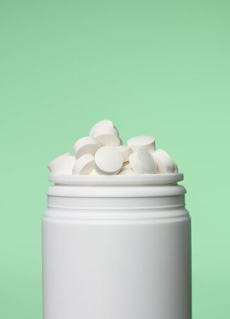 pastil: Can of pills toward green background Stock Photo