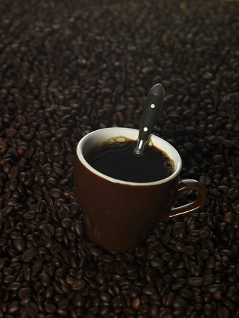 Cup of coffee among coffee beans photo