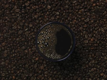 coffeebeans: Glass of coffee among coffee-beans Stock Photo